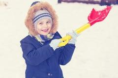 Ein Kind spielt mit Schnee mit einer Schaufel im Winter Lizenzfreies Stockbild