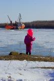 Ein Kind steht mit einem roten Ball und betrachtet das Schiff Stockfotografie