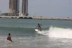 Ein Kind surfen die Wellen in Lagos-Strand, Bewunderer schauen an lizenzfreie stockfotos