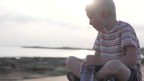 Ein Kind trinkt Wasser von einer Flasche auf dem Hintergrund eines Sonnenuntergangs im Meer stock footage