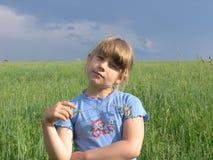 Ein Kind unter dunklem stürmendem Himmel Stockbilder