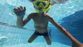 Ein Kind versucht zu schwimmen, eine tauchende Maske tragend stock video footage
