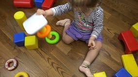 Ein Kind wirft mehrfarbige Plastikspielwaren auf dem Boden stock video footage