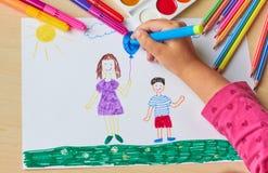 Ein Kind zeichnet ein farbiges Bild auf einem weißen Blatt Lizenzfreies Stockbild