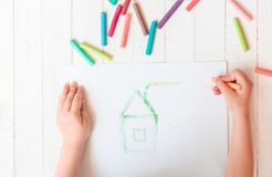 Ein Kind zeichnet ein Haus mit Zeichenstiften Haus Mehrfarbige Zeichenstifte, Pastell Stockfotos