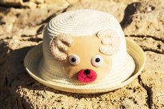 Ein Kinderhut von der Sonne in Form eines Bärnbären, der auf einem Felsen auf dem Strand, Strandkonzept liegt stockbild