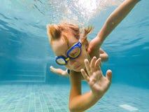 Ein Kinderjunge schwimmt unter Wasser in einem Pool, lächelt und hält Atem, mit schwimmenden Gläsern stockfotografie