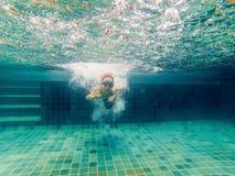 Ein Kinderjunge schwimmt unter Wasser in einem Pool, lächelt und hält Atem, mit schwimmenden Gläsern lizenzfreie stockfotos