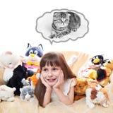 Ein Kindermädchen mit Spielzeug-Katzen Stockfotografie
