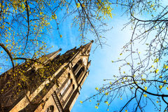 Ein Kirchturm, der durch Baumaste umgeben wird, wird gegen einen blauen Himmel mit Wolken eingestellt Stockfotografie