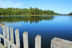 Ein klarer blauer See mit einem hölzernen Dock umgeben durch grünen Kiefernwald im Nordholz von Minnesota Lizenzfreies Stockfoto