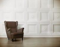Ein klassischer Lehnsessel gegen eine weiße Wand und einen Boden Lizenzfreies Stockbild