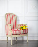 Ein klassischer Lehnsessel gegen eine weiße Wand und einen Boden Stockfotografie