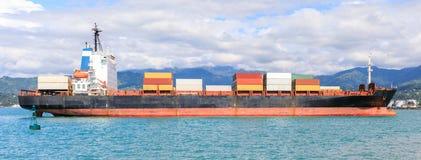 Ein kleiner Behälter im Hafen von Batumi auf einem Hintergrund von Bergen stockbilder