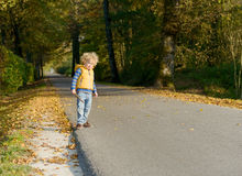 Ein kleiner blonder Junge auf der Seite einer kleinen Straße Lizenzfreies Stockbild