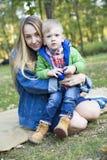 Ein kleiner blonder Junge in den Blicken einer grünen Jacke überrascht an Stockbild
