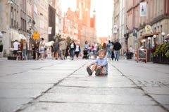 Ein kleiner blonder Junge, der auf einem Boden in einem Stadtzentrum sitzt Stockbild