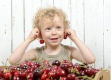 Ein kleiner blonder Junge, der Kirschen isst Stockfotografie