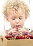 Ein kleiner blonder Junge, der Kirschen isst Lizenzfreie Stockfotos
