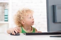 Ein kleiner blonder Junge, der mit Computer spielt Lizenzfreie Stockbilder