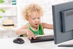 Ein kleiner blonder Junge, der mit Computer spielt Stockbilder