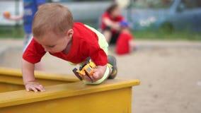 Ein kleiner blonder Junge, der mit defektem Traktor auf dem Spielplatz in der Zeitlupe spielt stock footage