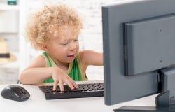 Ein kleiner blonder Junge, der mit der Tastatur spielt Lizenzfreie Stockfotos