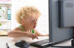 Ein kleiner blonder Junge, der mit einem Computer spielt Lizenzfreies Stockbild