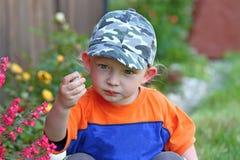 Ein kleiner blonder Junge, der mit einem Stein spielt Lizenzfreie Stockbilder