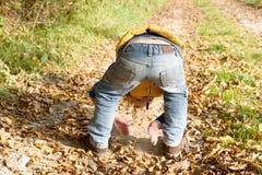 Ein kleiner blonder Junge, der mit Schmutz spielt Lizenzfreies Stockfoto