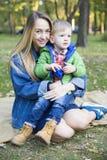 Ein kleiner blonder Junge in einer grünen Jacke, sitzend vor einem youn Stockfoto