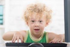 Ein kleiner blonder Junge mit einem Computer Stockbilder