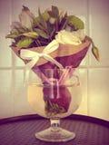Ein kleiner Blumenstrauß in einem Weinglas Stockfotos