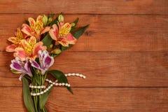 Ein kleiner Blumenstrauß von Alstroemeria mit einem Perlenthread auf hölzernem braunem Hintergrund Lizenzfreies Stockfoto