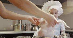 Ein kleiner Chef in einem weißen kulinarischen Hut spielt mit einem frischen Huhn in der Küche stock video