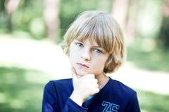 Ein kleiner denkender Junge draußen Stockbild