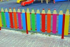 Ein kleiner farbiger dekorativer Zaun in Form von Bleistiften auf dem Spielplatz Lizenzfreies Stockbild