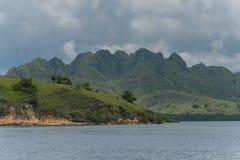 Ein kleiner Felsen bedeckt mit dem grünen Gras, das vom blauen Meerwasser Singapur späht Stockfotografie