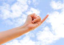 Ein kleiner Finger und eine Hand, die in Richtung zum Hintergrund des blauen Himmels erreichen Stockbilder