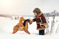 Ein kleiner glücklicher Junge in schneiendem Winter stockfoto