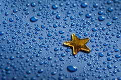 Ein kleiner goldener Stern und blaues Wasser dorops Stockfotos