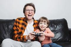 Ein kleiner hübscher Junge und sein Vati sitzen auf der Couch zu Hause und spielen Videospiele mit dem Steuerknüppel Vati und Soh lizenzfreie stockfotos