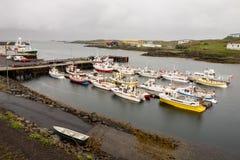 Ein kleiner Hafen in einer Stadt von Djupivogur, Island mit vielen Schiffchen Stockfotografie