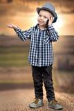 Ein kleiner Junge in den Gesprächen eines Hutes an seinem Handy Kleiner Chef stockbilder