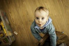 Ein kleiner Junge, der auf dem Boden nahe Schemel mit Spielwaren herum steht Stockfoto