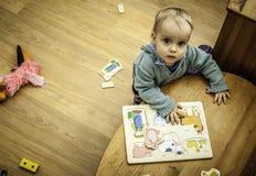Ein kleiner Junge, der auf dem Boden nahe Tabelle mit Spielwaren herum steht Lizenzfreie Stockfotos