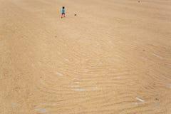 Ein kleiner Junge, der auf dem Trocknen des Reisfelds spielt stockfotos