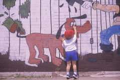 Ein kleiner Junge, der auf ein Graffitizeichen zeigt Lizenzfreie Stockfotos