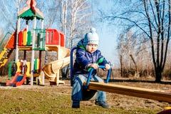 Ein kleiner Junge, der auf einem Rocker in einem Frühling Park schwingt stockbild