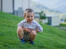 Ein kleiner Junge, der auf einer grünen Steigung sitzt stockfotos